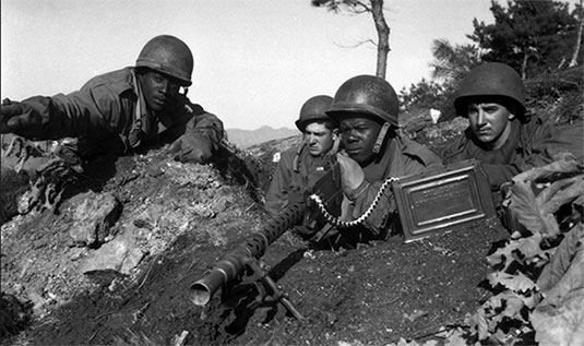 Fighting with 2nd Infantry Division north of the Chongchon River, Sergeant First Class Major Cleveland, weapons squad leader, points out communist-led North Korean position to his machinegun crew, November 20, 1950