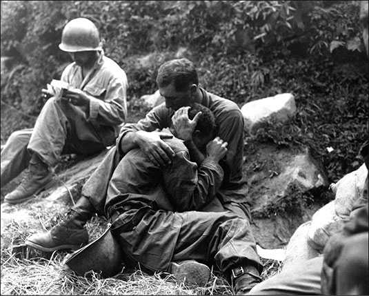 A grief-stricken American infantryman whose buddy has been killed in action is comforted by another Soldier. In the background, a corpsman methodically fills out casualty tags, Haktong-ni area, Korea, August 28, 1950