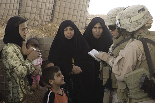 Lance Corporal Ashley Ramirez and Corporal Jessica L. Echeard of the Regimental Combat Team–2 Lioness Program check the passports of Iraqi women coming into the country at the Syrian Border in Waleed, Iraq, June 7, 2007. The Lionesses is an all-female unit organized to engage with Iraqi women at entry control points