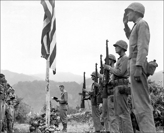"Lieutenant Colonel John Hopkins, commanding officer of the First Battalion, Fifth Marine Regiment, leads in singing the ""The Star Spangled Banner"" during memorial services held in the field during the Korean campaign, June 21, 1951"