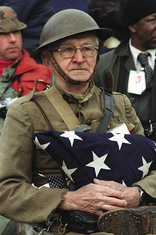 Joseph Ambrose, an 86-year-old World War I veteran, attends the dedication day parade for the Vietnam Veterans Memorial in Washington, DC, November 13, 1982. He is holding the flag that covered the casket of his son, who was killed in the Korean War