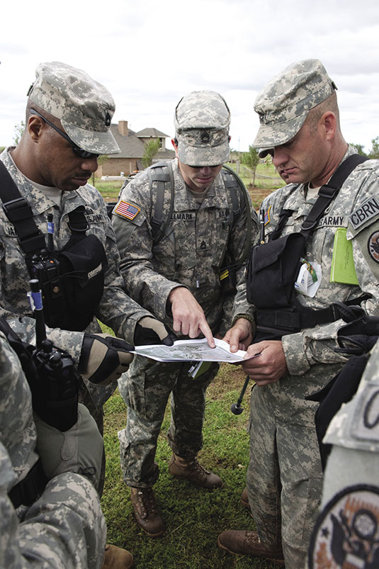 Sergeant 1st Class Lawrence Jarrett (left), of Spencer, Oklahoma, Sergeant 1st Class Jared Hallmark (center), of Choctaw, Oklahoma, and Master Sergeant Ken Perry (right), of Shawnee, Oklahoma, review a map of the area they are about to search for a missing 3-year-old boy. All three are members of the 63rd Civil Support Team, Oklahoma National Guard. The missing boy was pulled from his house by a tornado on May 24 (Geoff Legler)
