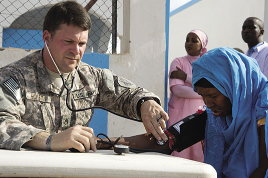 Staff Sergeant Matthew Hoffman, 448<span class='endnote'>th </span>Civil Affairs Battalion noncommissioned officer in charge of operations, performs a blood pressure check on a patient during a Medical Civic Action Program clinic in Chebelley, Djibouti, October 6, 2012