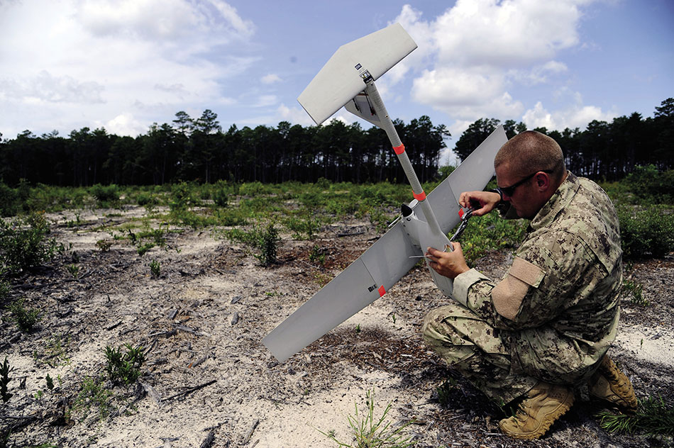 Airman fastens GPS mechanism inside RQ-11B Raven B hand-launched remote-controlled unmanned aerial vehicle (U.S. Air Force/Gustavo Castillo)