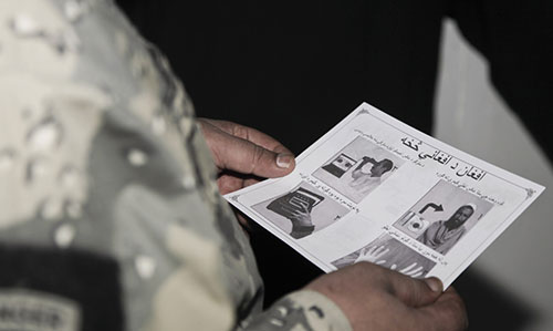 Border police at Wesh review information flier about Afghan 1000 Biometrics Facility (U.S. Army/Joseph Johnson)