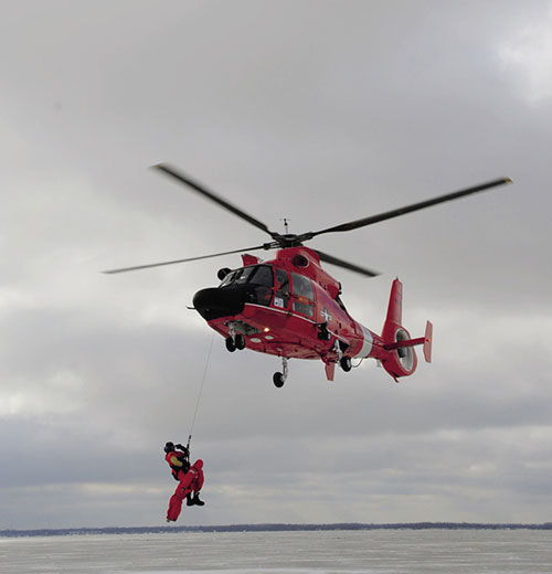 U.S. Coast Guard rescue swimmer deploys from MH-65C Dolphin during mass rescue exercise Icy Resolve 2013 (U.S. Coast Guard)