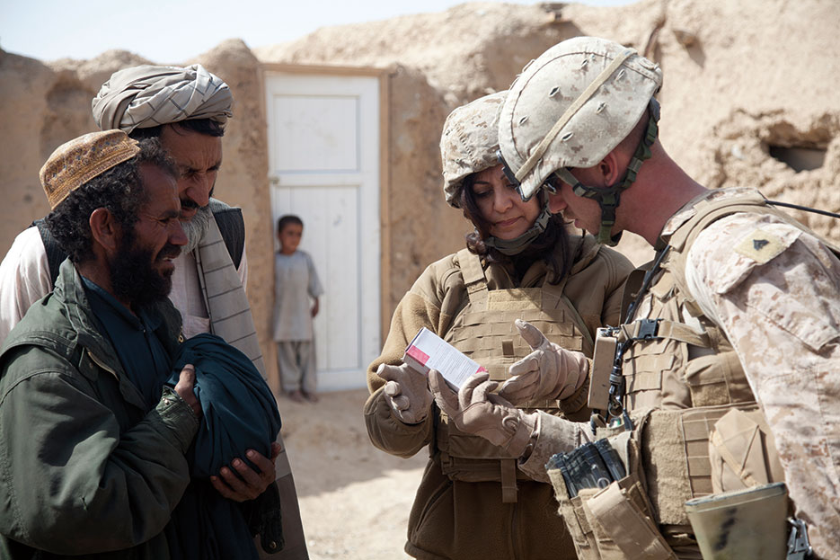 Marine Corps linguist for Female Engagement Team 11-2, Task Force Leatherneck, explains how to care for wound at district center in Delaram, Nimroz Province, Afghanistan (U.S. Marine Corps/Catie D. Edwards)