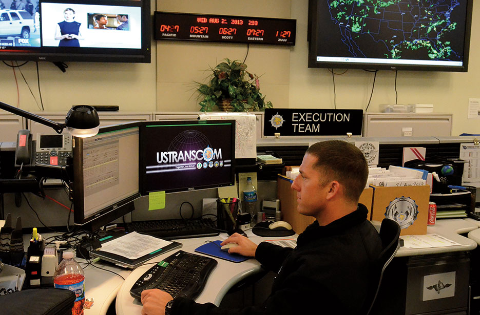 Sailor monitors flights in Joint Operational Support Airlift Center Execution Team area of USTRANSCOM Fusion Center (USTRANSCOM/Bob Fehringer)