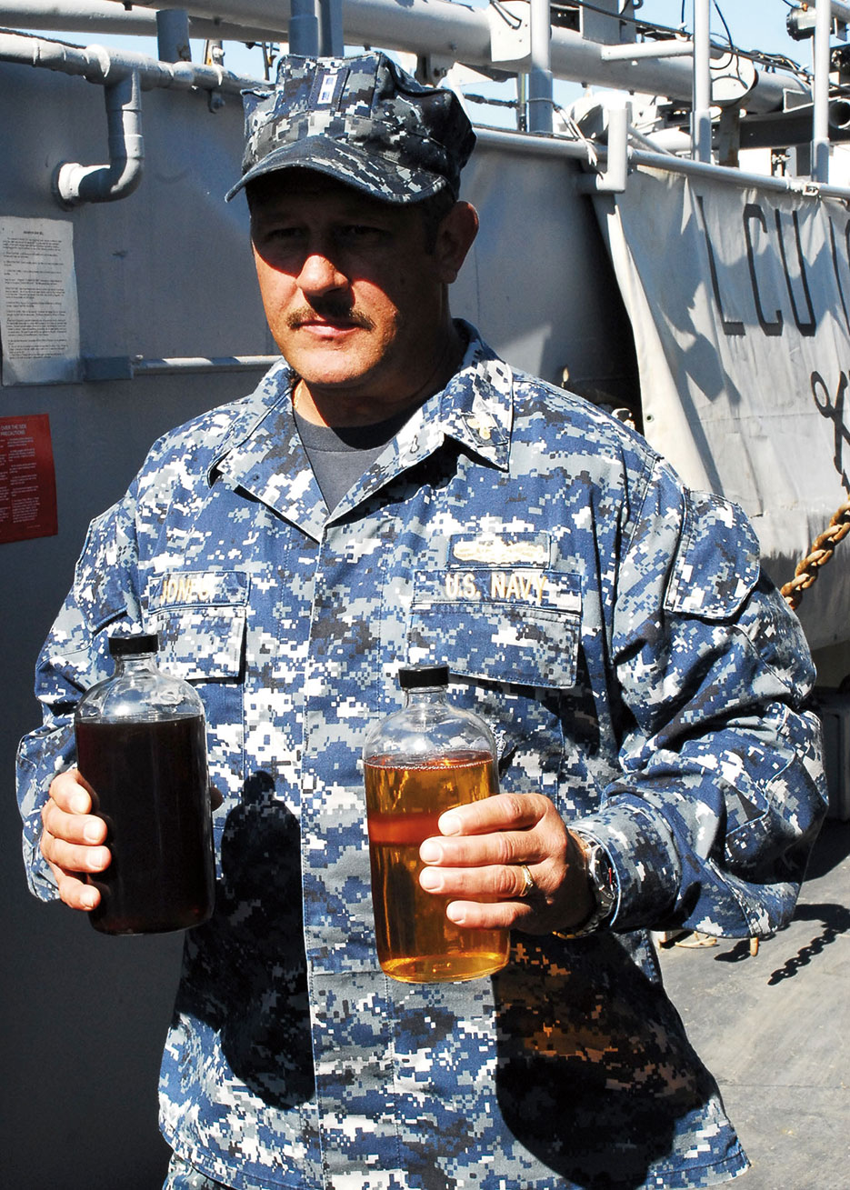 Sailor presents samples of traditional F-76 diesel fuel and 50/50 biofuel blend to illustrate use of biofuels in support of Navy Secretary's goal to cut petroleum consumption in half by 2015 (U.S. Navy/Lolita Lewis)