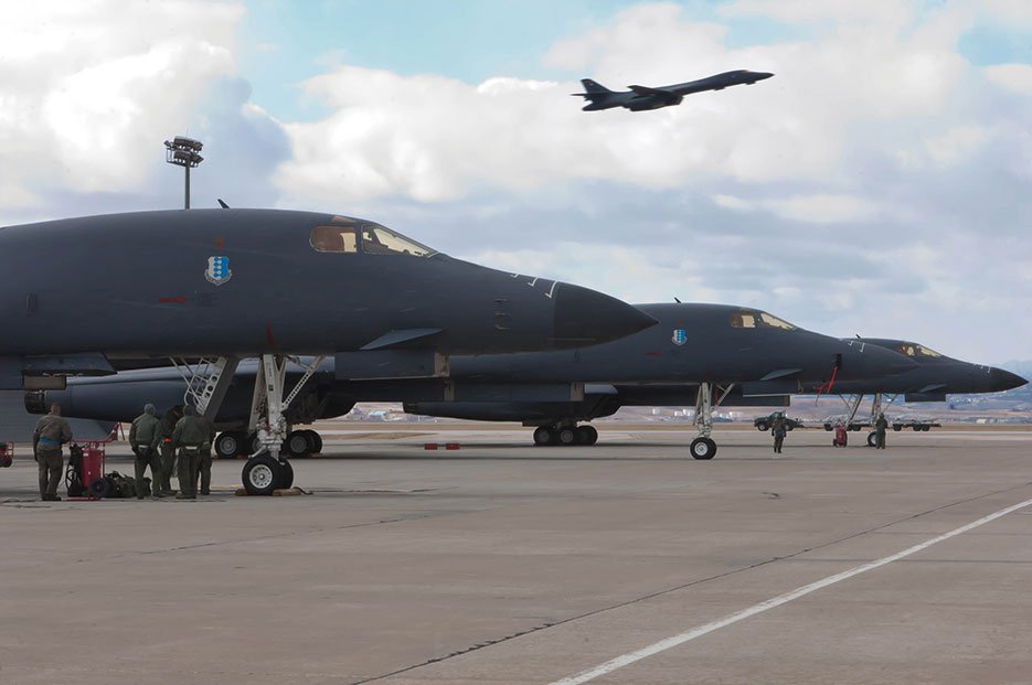 Air Force crews perform preflight checks as B-1 Lancer flies overhead during operational readiness exercise at Ellsworth Air Force Base (U.S. Air Force/Zachary Hada)