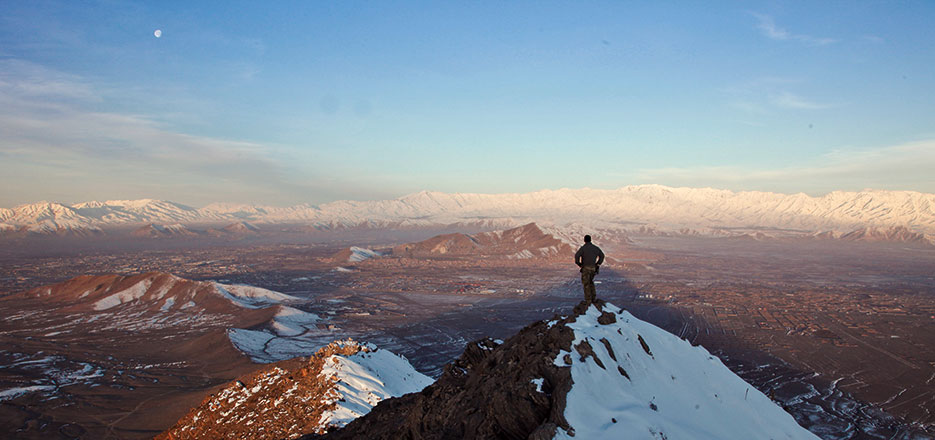 Member of coalition force surveys terrain in Kabul Province, Afghanistan (U.S. Army/Matthew Freire)