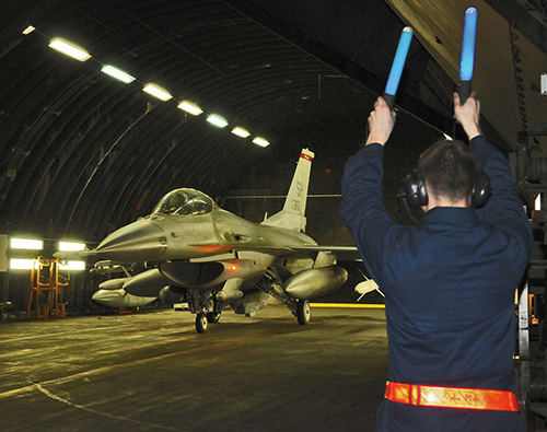 Crew chief marshals F-16 Fighting Falcon from hardened aircraft shelter in Germany in support of Operation Odyssey Dawn (U.S. Air Force/Benjamin Wilson)