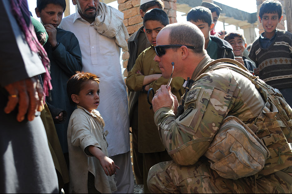 Medic conducts checks with Afghan children in Khowst Province (U.S. Army/Jason Epperson)