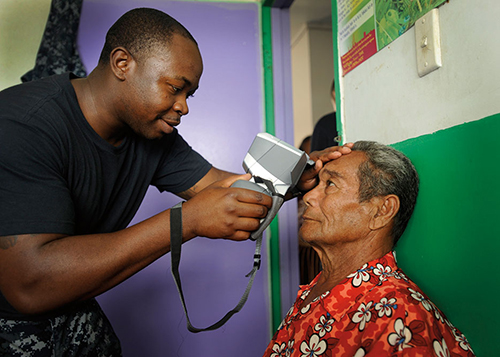 Corpsman uses auto refractor during eye examination at Prince Ngu Hospital in Tonga during Pacific Partnership 2011 (U.S. Navy/Eli J. Medellin)