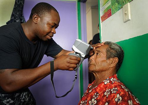Corpsman uses auto refractor during eye examination at Prince Ngu Hospital in Tonga during Pacific Partnership 2011 (U.S. Navy/Eli J. Medellin)