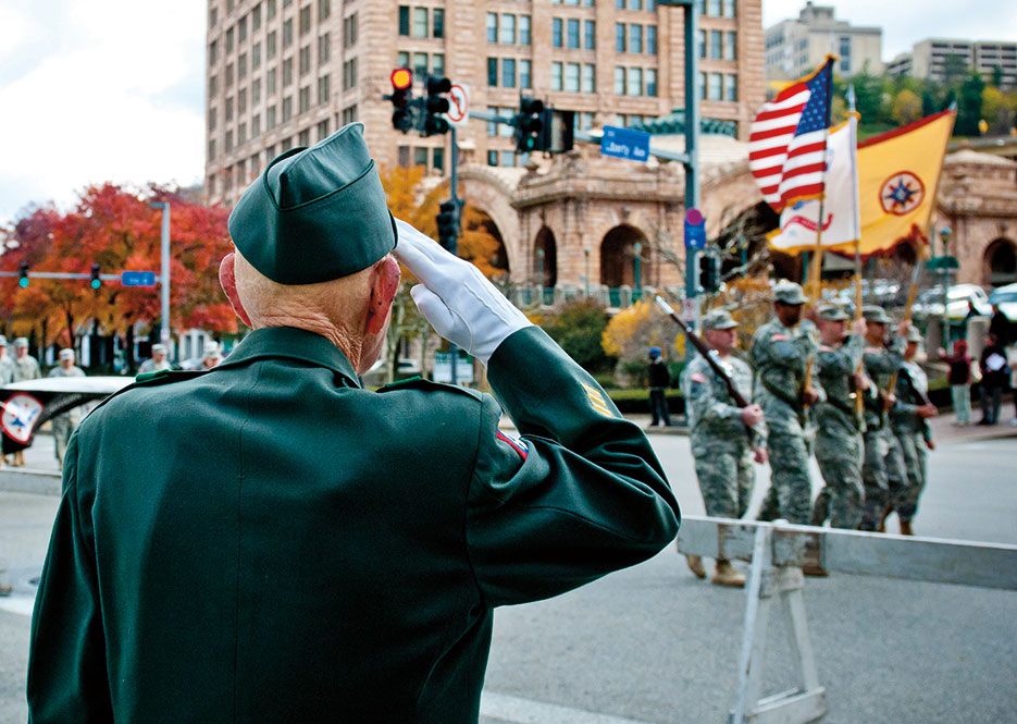 Retired Army 1st Sgt. William Staude of Elliott, Pennsylvania, salutes Soldiers from 316th Expeditionary Sustainment Command stationed in Coraopolis, Pennsylvania, as they march past him during Veterans Day parade in downtown Pittsburgh, November 2011 (U.S. Army/Michael Sauret)