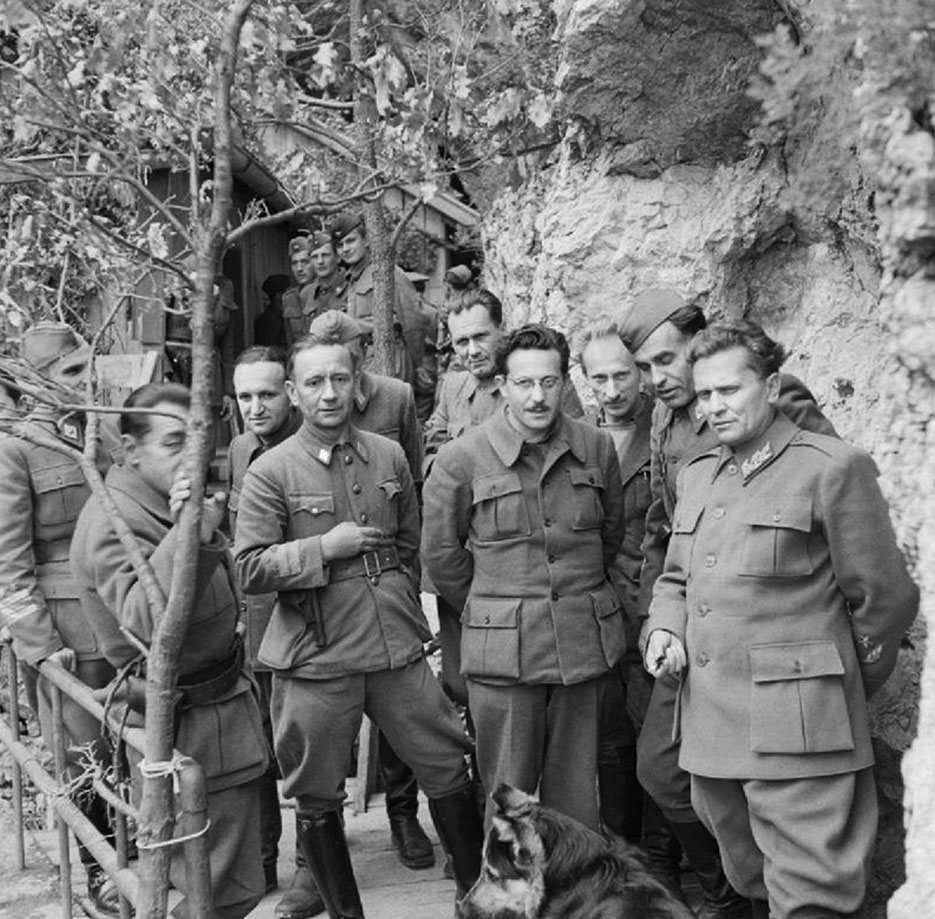 Marshal Josip Tito (right) stands with his Cabinet Ministers and Supreme Staff at his mountain headquarters in Yugoslavia on May 14, 1944 (Imperial War Museum)