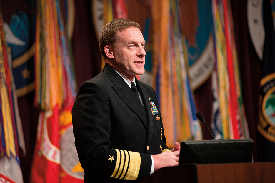 Admiral Michael Rogers addresses audience and workforces of U.S. Cyber Command, National Security Agency, and Central Security Service at his assumption of command ceremony, April 2014 (National Security Agency)