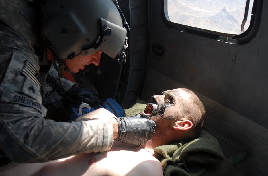 Flight medic treats Soldier from 1st Stryker Brigade Combat Team, 25th Infantry Division, while en route to Kandahar Airfield for additional treatment (DOD)