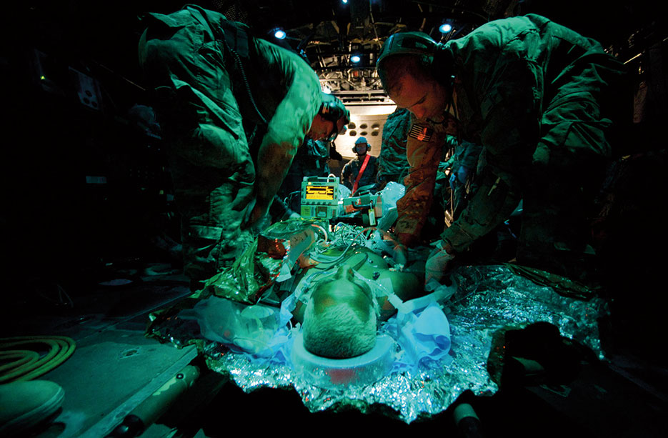 Aeromedical evacuation technician with 651<sup>st</sup> Expeditionary Aeromedical Evacuation Squadron checks on Afghan man in critical but stable condition for transport, Forward Operating Base Tarin Kowt, Afghanistan (U.S. Air Force/Greg Biondo)