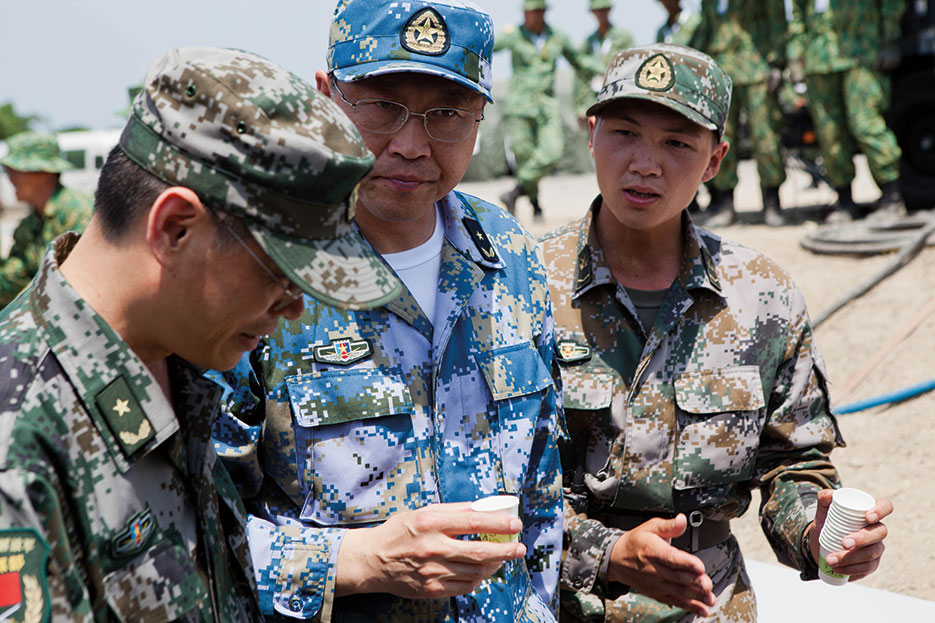 PLAN rear admiral drinks sample of purified water at disaster site in Biang, Brunei Darussalam, as engineers with China, Singapore, and the United States demonstrate water purification capabilities (U.S. Marines/Kasey Peacock)