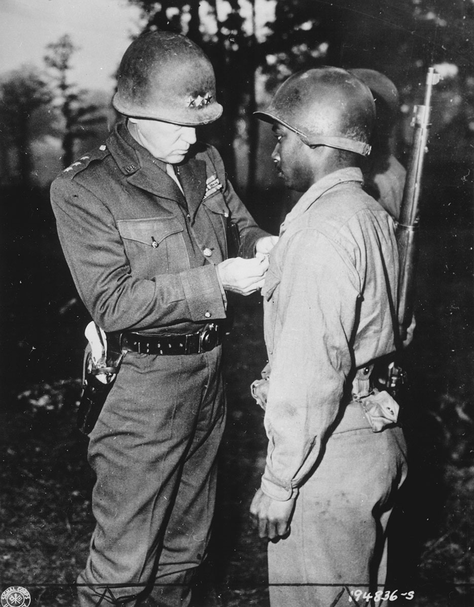 Lieutenant General George S. Patton, U.S. Third Army commander, pins Silver Star on Private Ernest A. Jenkins of New York City (NARA)