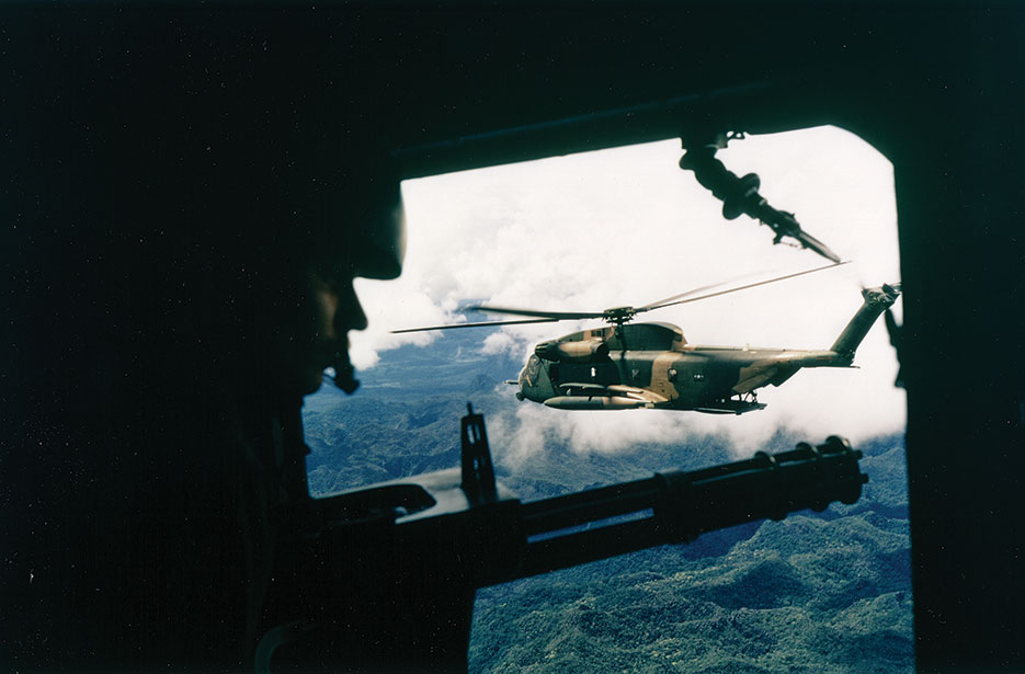 Side view of HH-53 helicopter of 40th Aerospace Rescue and Recovery Squadron as seen from gunner's position on A-1 of 21st Specialist Operations Squadron (U.S. Air Force)