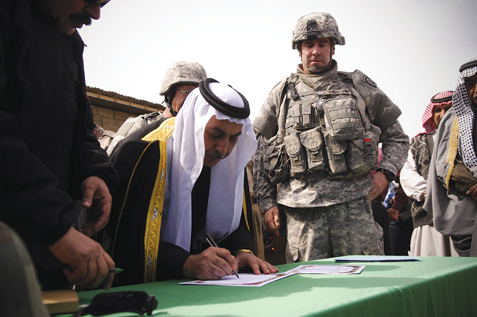 Sheik Abdullah Sami Obeidi, a Sunni Arab tribal leader, signs declaration of support for Sons of Iraq program as U.S. Army Colonel David Paschel, commander of 1st Brigade Combat Team, 10th Mountain Division, looks on in Al Noor, Iraq, March 9, 2008 (DOD/Samuel Bendet)