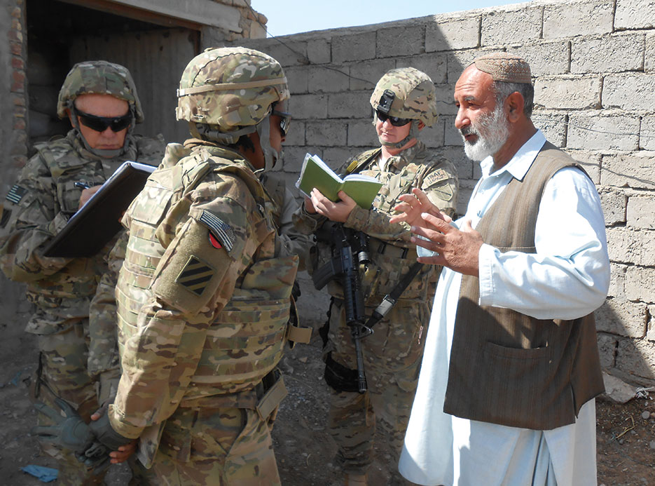 Civilian Expeditionary Workforce member engages local business owner in discussion regarding poultry feed production, Kandahar Province (Kentucky National Guard/Dallas Kratzer)