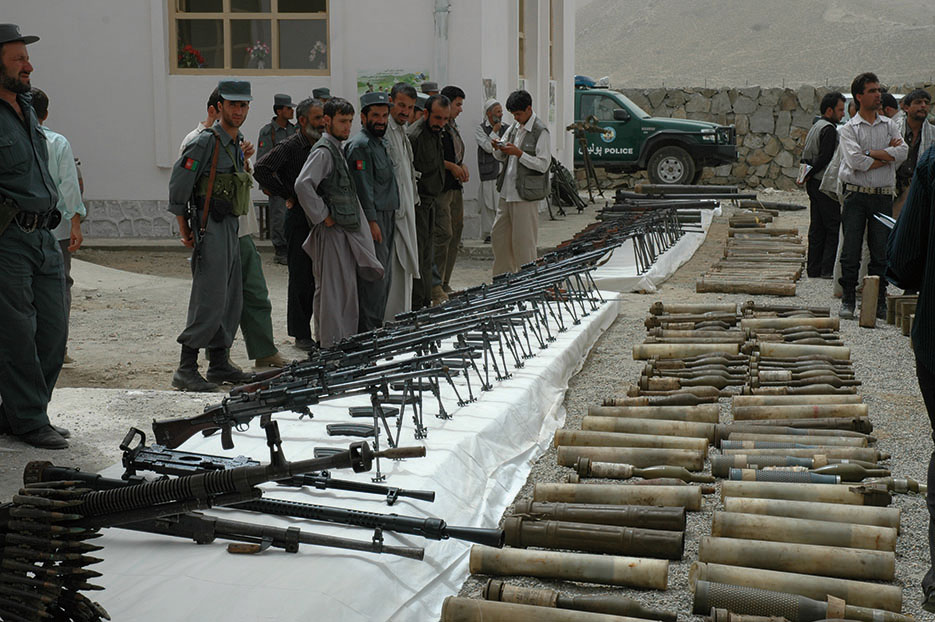 Local police, government leaders, and villagers gather outside new Anaba District Center in Panjshir Province, Afghanistan, August 11, 2008, to view weapons turned in through Disbandment of Illegal Armed Groups program (DOD/Jillian Torango)