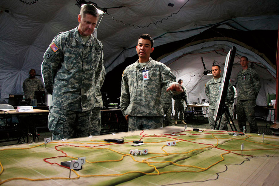 Intelligence analyst gives commander of 21st Theater Sustainment Command terrain brief of Hohenfels Training Area on enemy activity (U.S. Army/Henry Chan)