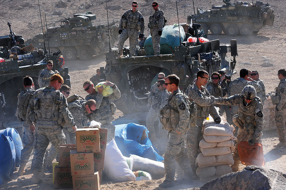 U.S. Soldiers assigned to Company C, 1st Battalion, 17th Regiment, unload humanitarian aid for distribution to town of Rajan Kala, Afghanistan, December 5, 2009 (U.S. Air Force/Francisco V. Govea II)