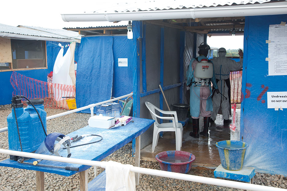Worker decontaminates caregiver leaving patient area of active Ebola treatment center built as part of Operation United Assistance in Suakoko, Liberia, November 22, 2014 (U.S. Army/Brien Vorhees)