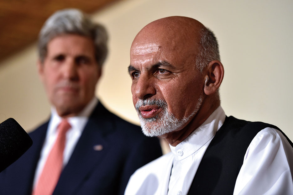John Kerry listens as Afghan presidential candidate Ashraf Ghani addresses reporters at UN Mission Headquarters in Kabul, Afghanistan, July 2014 (State Department)