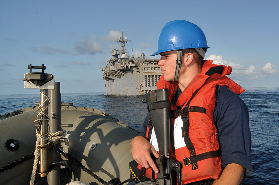 Seaman stands force protection watch in 7-meter rigid hull inflatable boat while amphibious transport dock ship USS <i>Ponce</i> (LPD 15) gets under way after port visit at Seychelles, November 2010 (U.S. Navy/Nathanael Miller)