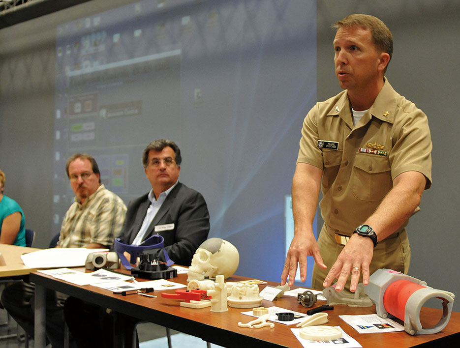 Captain Frank Futcher explains display of 3D-printed objects during Navy Warfare Development Command–sponsored innovation workshop at Old Dominion University in Norfolk, Virginia (U.S. Navy/Jonathan E. Donnelly)