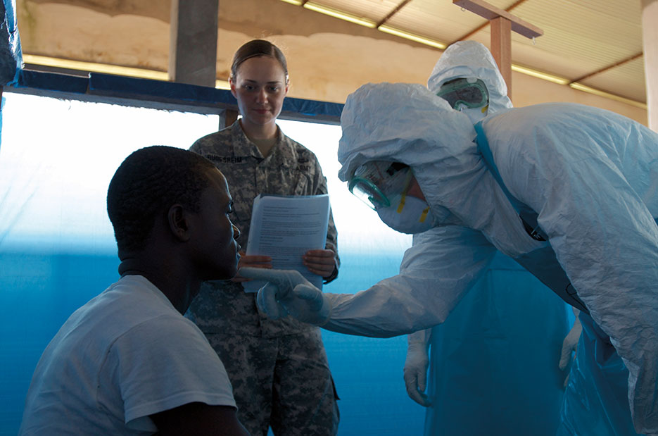 Students in Ebola Treatment Unit Course led by Joint Force Command–United Assistance, diagnose potential patient for symptoms of virus during scenario training, Monrovia, Liberia, November 20, 2014 (U.S. Army/V. Michelle Woods)