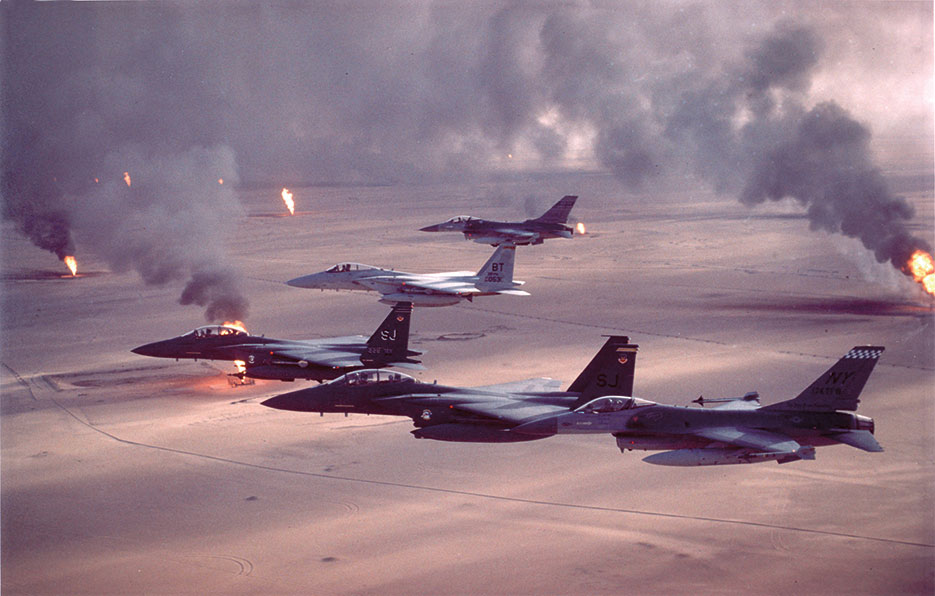 Air Force F-16A Fighting Falcon, F-15C Eagle, and F-15E Strike Eagle fighter aircraft fly over burning oil field sites in Kuwait during Operation <i>Desert Storm</i> (U.S. Air Force)