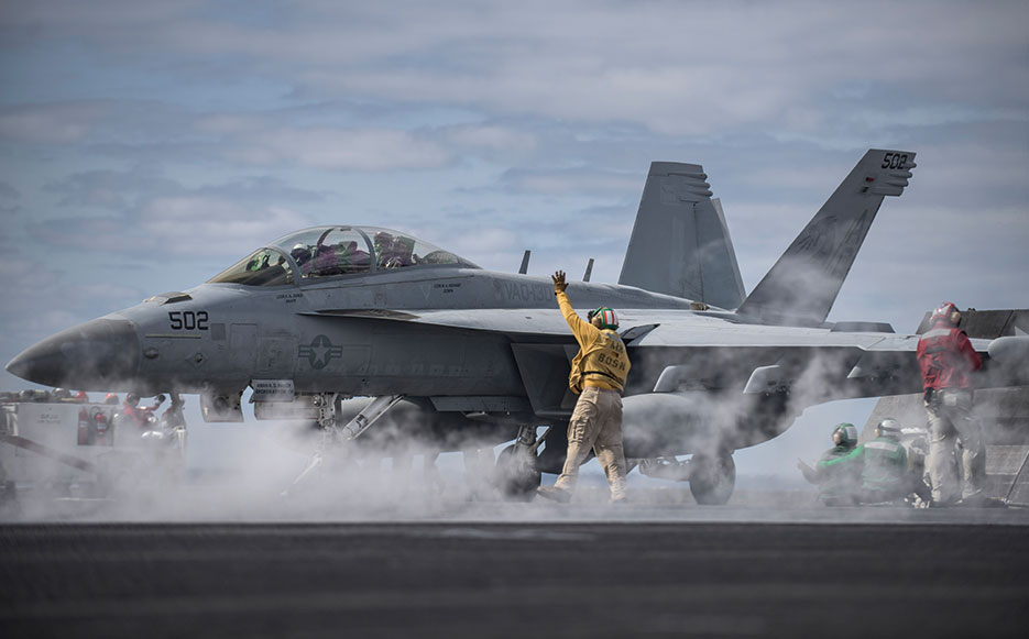 Chief Warrant Officer 3 signals to E/A-18G Growler on flight deck of aircraft carrier USS Dwight D. Eisenhower, April 11, 2016 (U.S. Navy/J. Alexander Delgado)