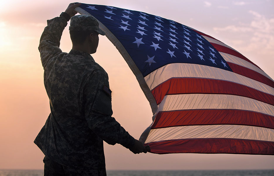 Soldier with Joint Forces Command–United Assistance, assigned to Headquarters and Headquarters Battalion, 101st Airborne Division (Air Assault), holds up U.S. flag during promotion and reenlistment ceremony, January 1, 2015, at Barclay Training Center, Monrovia, Liberia (U.S. Army/Rashene Mincy)