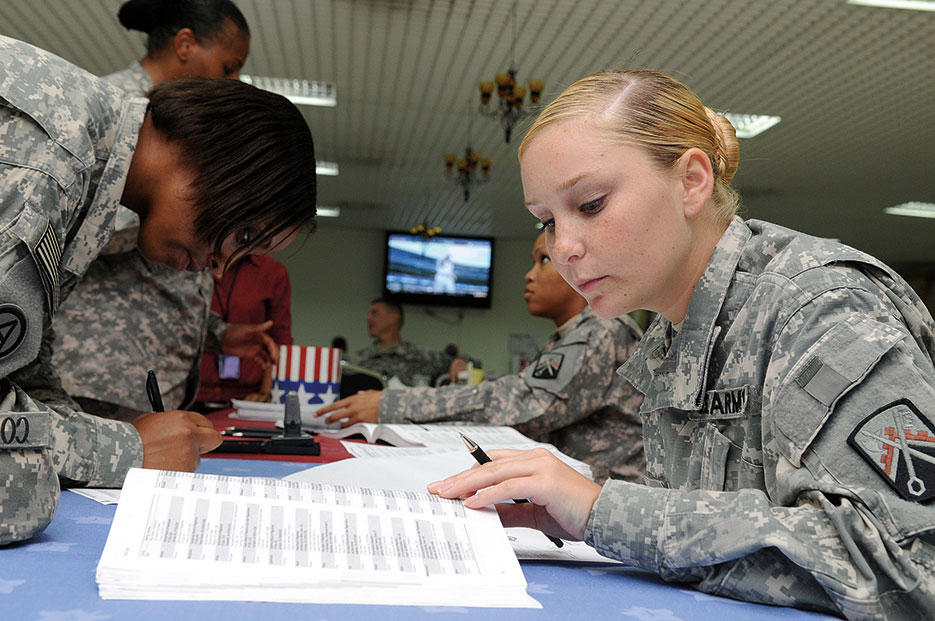 Soldier fills out absentee ballot form during voting assistance drive at Camp As Sayliyah, Qatar (U.S. Army/Dustin Senger)