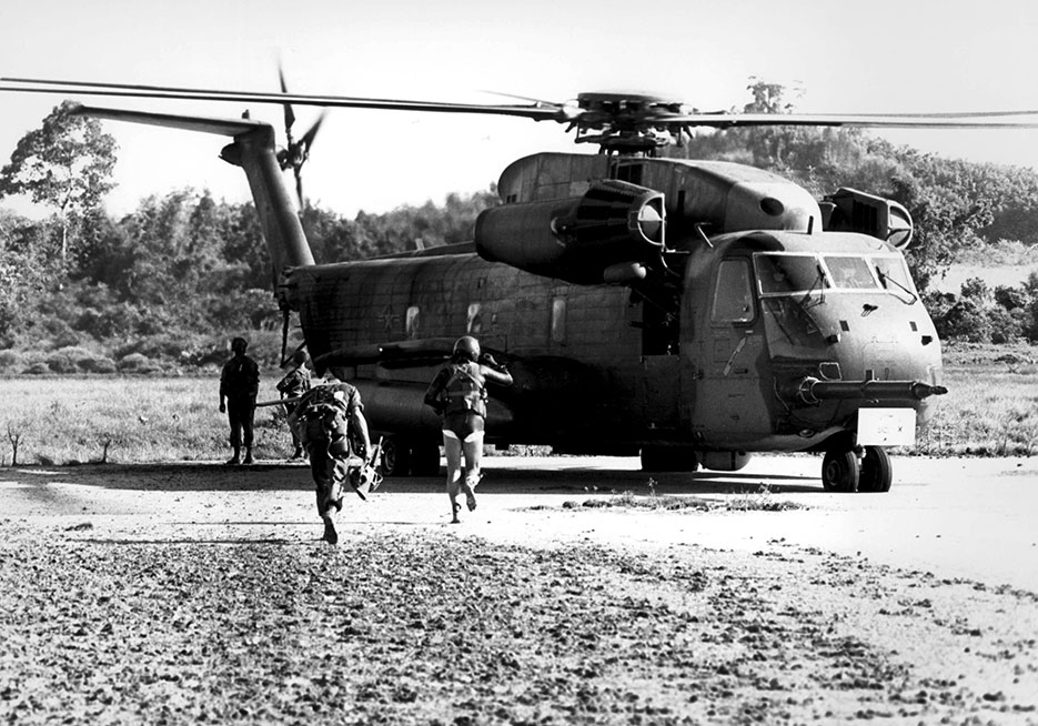 Marine and Air Force pararescueman of 40th Aerospace Rescue and Recovery Squadron (in wet suit) run for Air Force helicopter during assault on Koh Tang Island to rescue U.S. merchant ship SS Mayaguez and crew, May 15, 1975 (DOD)