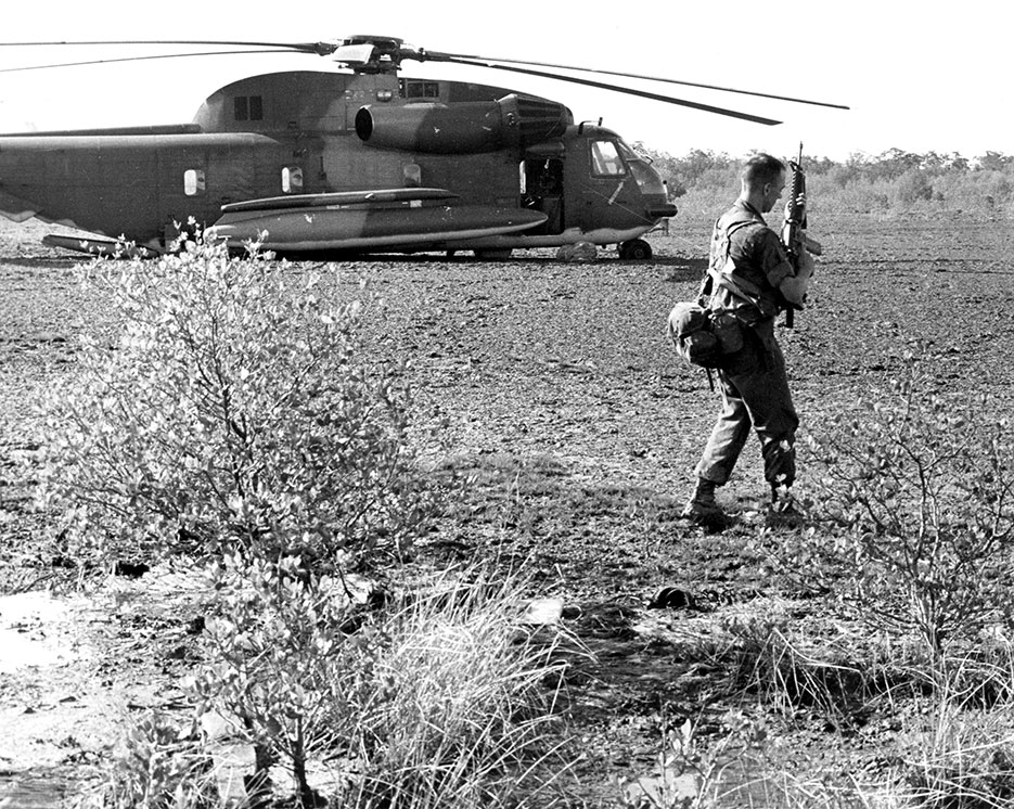 Marine captain prepares to fire on and destroy important equipment on disabled HH-53 to prevent its capture by Cambodians (U.S. Air Force/Ronald T. Rand)