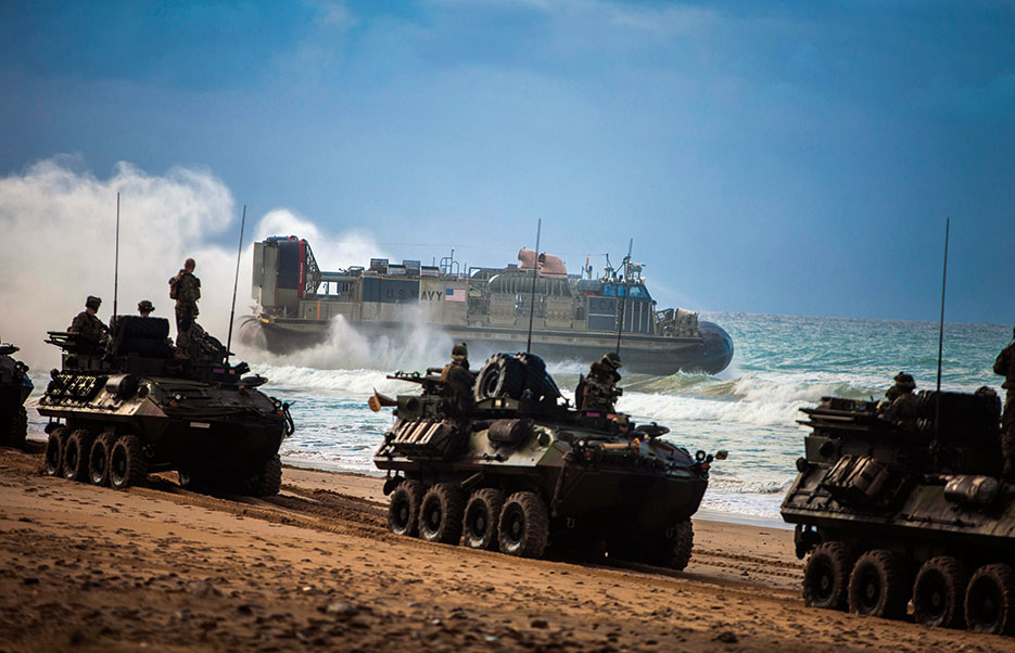 Marines with Battalion Landing Team, 1st Battalion, 6th Marine Regiment, 22nd Marine Expeditionary Unit, convoy light-armored vehicles across beach as Navy landing craft, air cushion with Assault Craft Unit 4, departs beach of Sierra del Retin, Spain, during Spanish Amphibious Bilateral Exercise 2014, February 24, 2014 (U.S. Marine Corps/Austin Hazard)