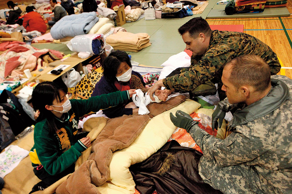 As part of Operation Tomodachi, U.S. Navy physician with III Marine Expeditionary Force (Forward) examines Japanese woman in school being used as internally displaced persons camp for residents affected by earthquake and tsunami that struck mainland Japan, March 11, 2011 (DOD)