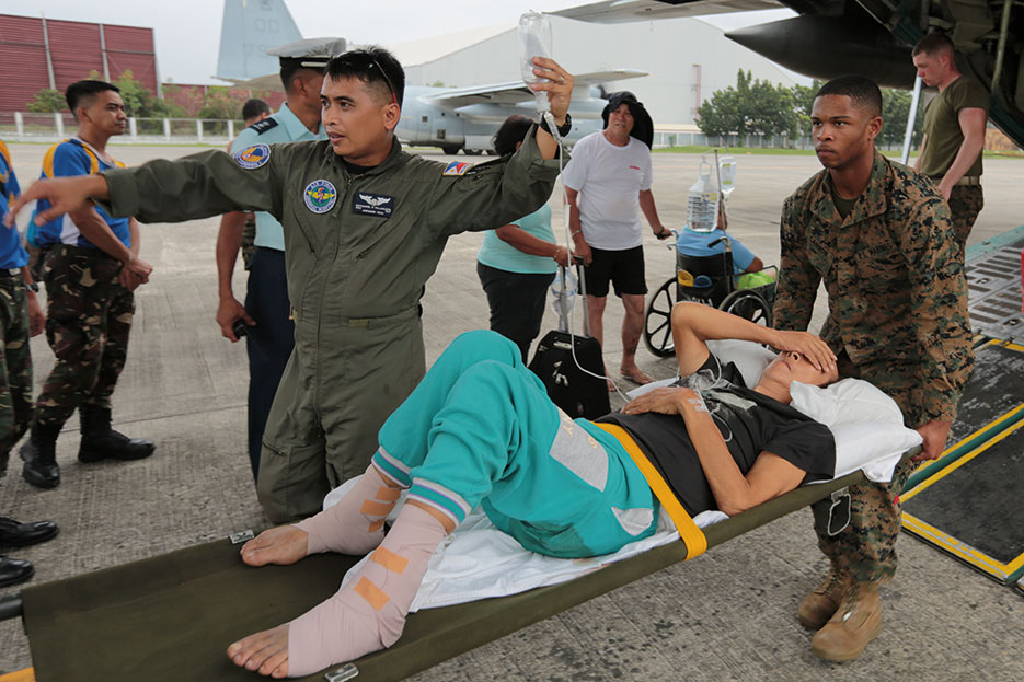 Marines carry injured Filipino woman on stretcher for medical attention at Villamor Air Base, Philippines, November 11, 2013 (DOD/Caleb Hoover)