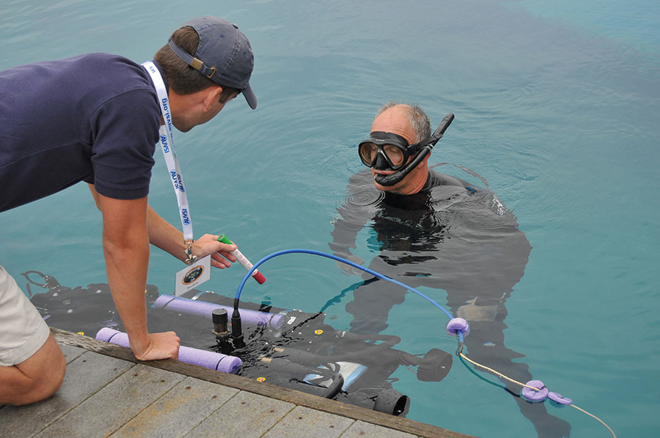 "Space and Naval Warfare Systems Center Pacific diver assists University of Florida team member with in-water checks to university's ""Subjugator"" Autonomous Underwater Vehicle during 14th Annual International RoboSub Competition, July 13, 2011 (U.S. Navy/Rick Naystatt)"