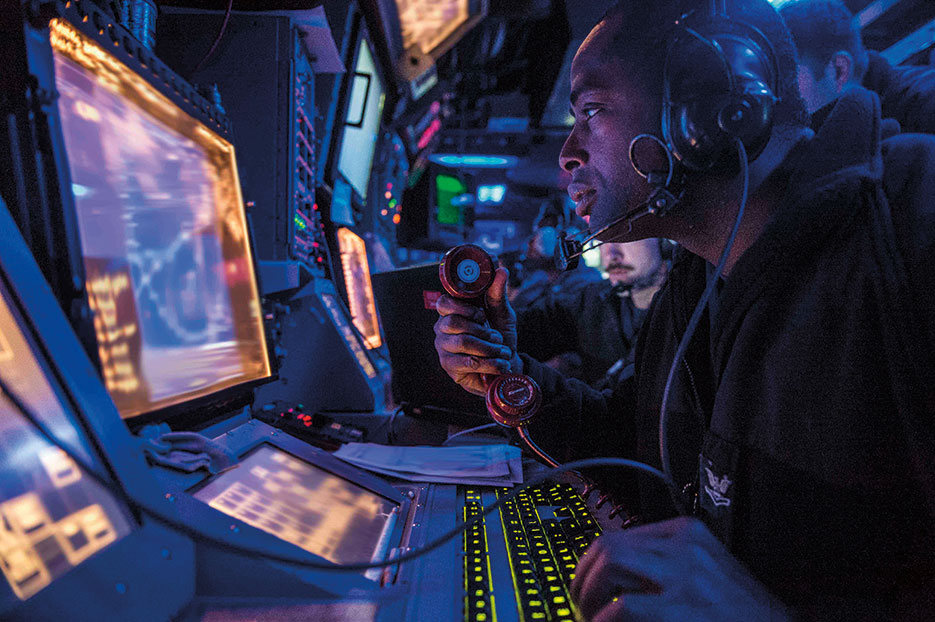 Sailor assigned to USS Mustin stands watch in ship's combat information center during Exercise Valiant Shield 2014, which integrates about 18,000 U.S. Navy, Air Force, Army, and Marine Corps personnel, more than 200 aircraft, and 19 surface ships for real-world joint operational experience, September 16, 2014 (U.S. Navy/Declan Barnes)