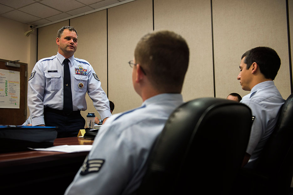 Professional military education instructor, 62nd Airlift Wing, speaks with students about results of their graded assignment, August 26, 2015, at Julius A. Kolb Airman Leadership School at Joint Base Lewis-McChord, Washington (U.S. Air Force/Sean Tobin)