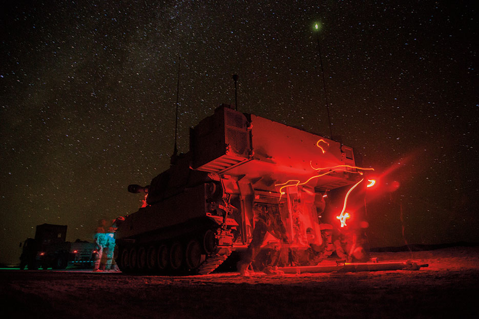 Soldiers assigned to Bravo Company, 1st Battalion, 77th Armor Regiment, 4th Armored Brigade Combat Team, 1st Armored Division, provide security with a M109A6 Paladin prior to reconnaissance patrol during Decisive Action Rotation 14-10 at National Training Center at Fort Irwin, California, September 24, 2014 (U.S. Army/Richard W. Jones, Jr.)